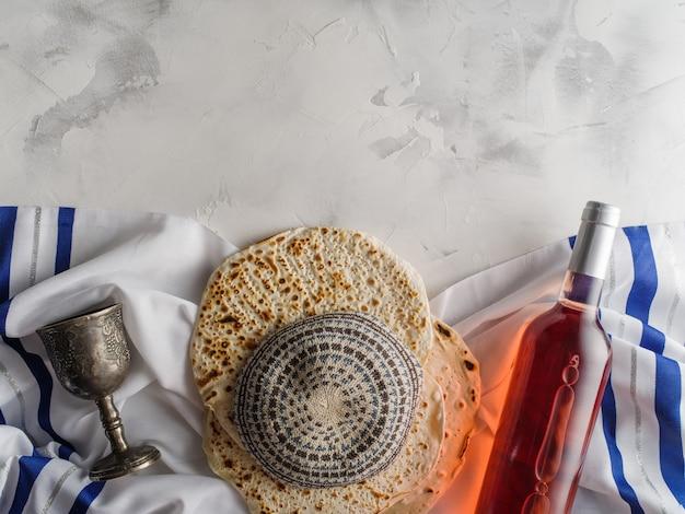 Pasqua festa tradizionale celebrazione con tazza di vino kosher matzah pane azzimo su pesach ebraica, copyspace. lay piatto.