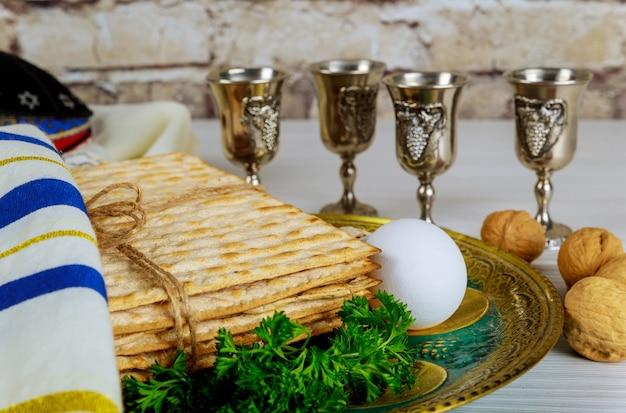Celebrazione tradizionale della festa della pasqua ebraica con quattro tazze di vino kosher matzah pane azzimo sulla pesach ebraica