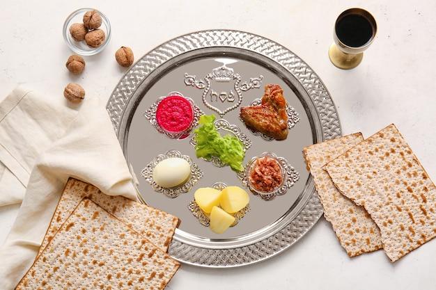 Piatto di seder pasquale con cibo tradizionale su superficie bianca