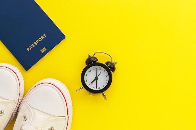 Passaporto, sveglia e scarpe di gomma su sfondo giallo. tempo di viaggiare. accessori da viaggio. vacanza e concetto di vacanza. vista dall'alto, piatto con spazio di copia.
