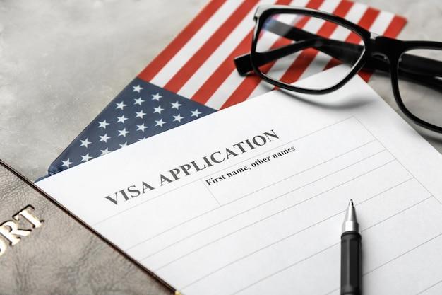 Passaporto, bandiera americana e modulo per la domanda di visto sul tavolo. immigrazione negli usa