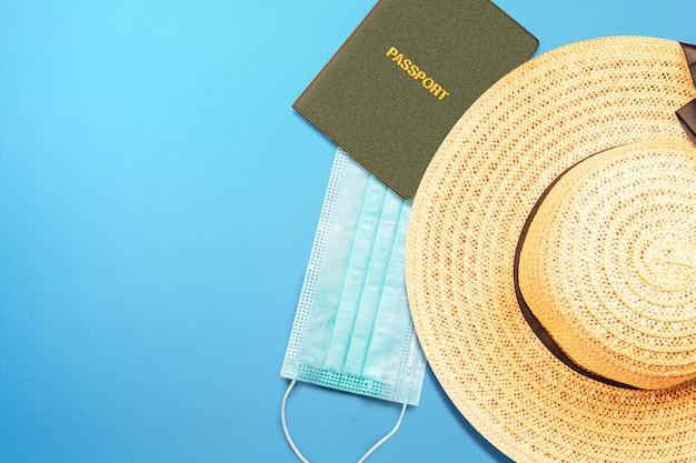 Passaporto e cappello con maschera su una superficie colorata. viaggiare nella nuova normalità