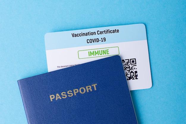 Passaporto e certificato di vaccinazione su un tavolo blu