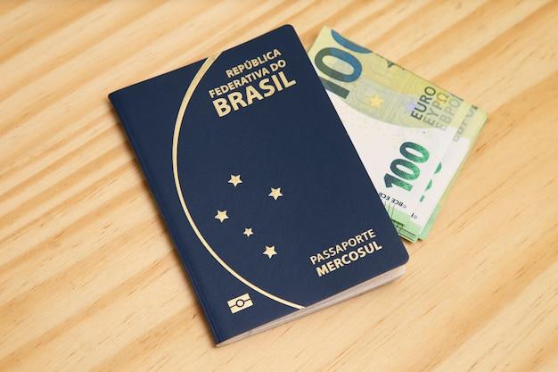 Passaporto con 100 banconote in euro sul lato, sul tavolo di legno. Foto Premium