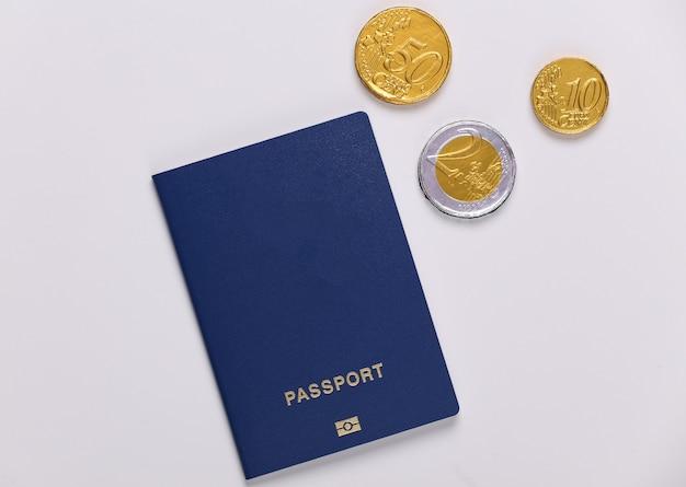 Passaporto con monete su un bianco. concetto di viaggio o emigrazione