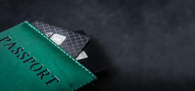 Passaporto con carte di credito su sfondo scuro con spazio copia da vicino