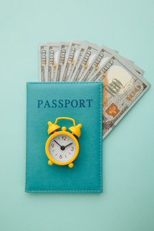Passaporto con banconote in denaro e sveglia sull'azzurro.