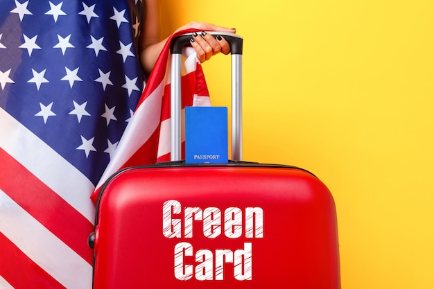 Passaporto con bandiera usa sulla valigia rossa, concetto di carta verde
