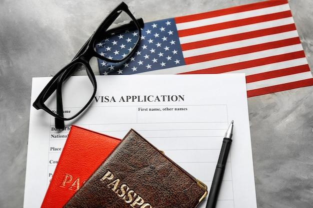 Passaporti, bandiera americana e modulo per la domanda di visto sul tavolo. immigrazione negli usa
