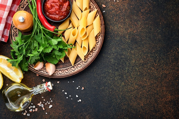 Sfondo di pasta. pasta rigati, salsa ketchup, olio d'oliva, spezie, prezzemolo e pomodori freschi su un tavolo di ardesia scuro. sfondo di cottura del cibo. vista dall'alto con copia spazio.