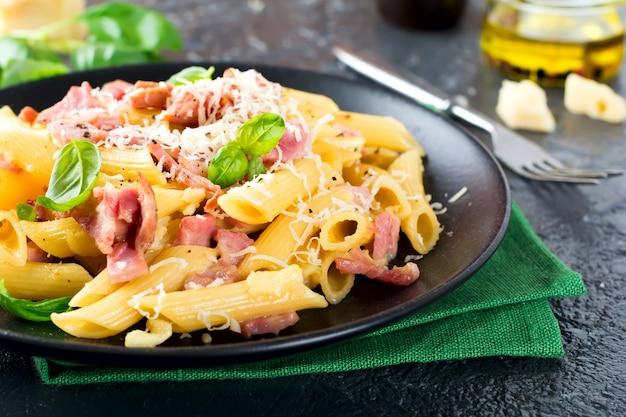 Pasta alla carbonara con prosciutto e parmigiano sulla tavola nera.