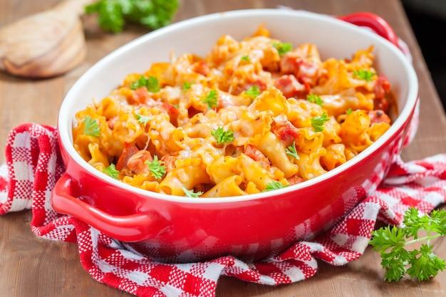 Casseruola di pasta con pancetta, prosciutto, formaggio e salsa di pomodoro