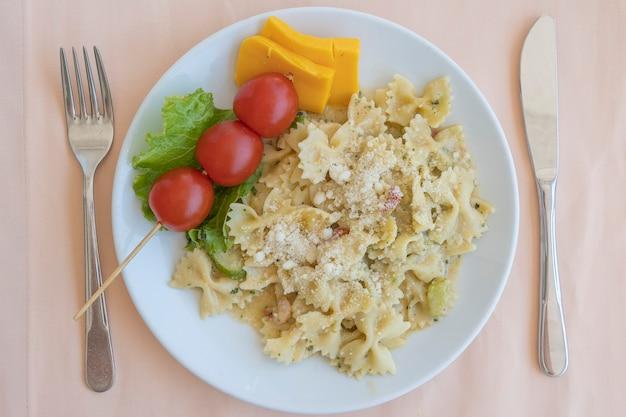 Farfalle di pasta con pomodorini e formaggio in piatto bianco, primo piano