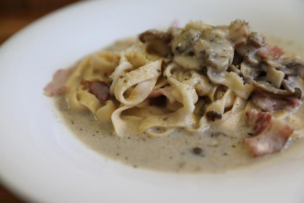 Pasta fettuccine alfredo salsa bianca con prosciutto, pancetta e funghi