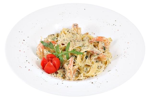 Fettuccine di pasta con gamberetti sul piatto bianco, isolato su sfondo bianco.