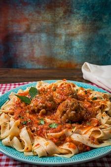 Pasta o fettuccine con salsa di pomodoro e polpette in un piatto rustico su una tovaglia a quadretti.
