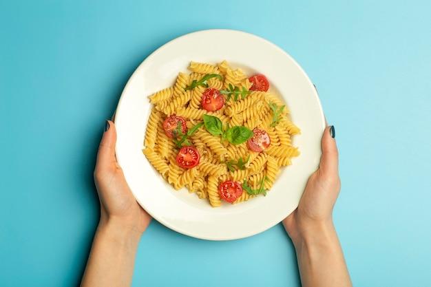 Cibo pasta su uno sfondo blu con mani femminili. pasta italiana fusilli con pomodori e basilico su un piatto bianco. h