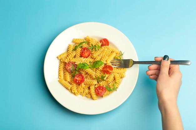 Cibo pasta su uno sfondo blu con mani femminili. pasta italiana fusilli con pomodori e basilico su un piatto bianco.