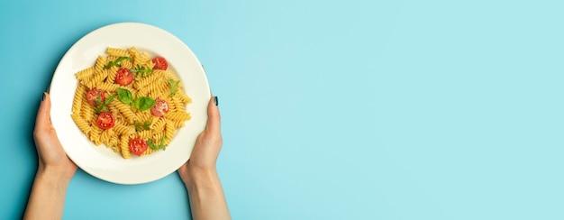 Cibo di pasta su uno sfondo blu banner con mani femminili. pasta italiana fusilli con pomodori e basilico su un piatto bianco.