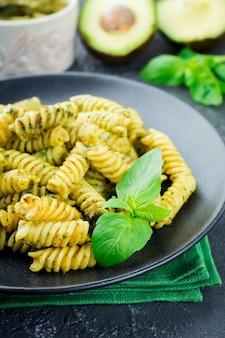 Fusilli di pasta con salsa di basilico avocado verde e ingredienti sulla tavola nera. copia spazio.