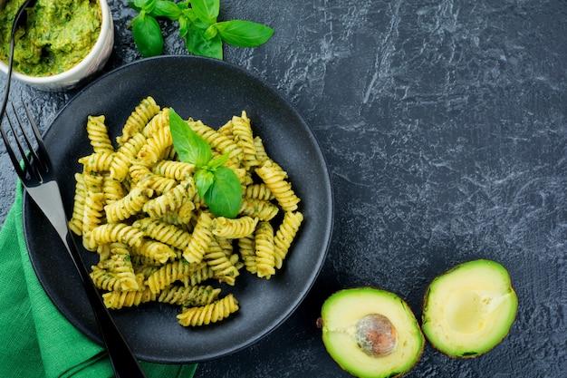 Fusilli di pasta con salsa di basilico avocado verde e ingredienti sulla tavola nera. vista dall'alto. copia spazio.