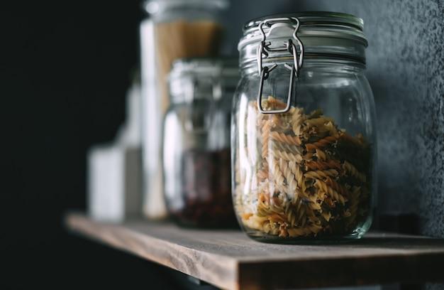 Pasta e drogheria in barattoli di vetro su uno scaffale di legno in cucina. dettaglio
