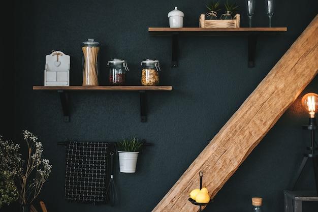 Pasta e drogheria in barattoli di vetro su uno scaffale di legno in cucina.