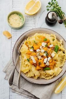Pasta mafaldine napoletane con zucca al forno, formaggio feta ed erbe aromatiche nel piatto di ceramica sulla tavola di legno bianca. stile rustico. vista dall'alto.
