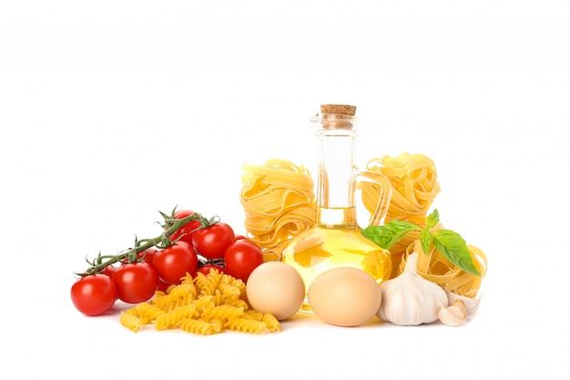 Pasta, olio d'oliva, pomodori, uova e aglio isolati su bianco. pasta integrale non cotta