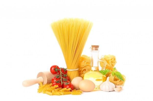 Pasta, olio d'oliva, pomodori, uova, matterello ed aglio isolati su bianco. pasta integrale non cotta
