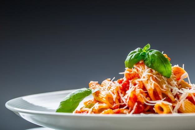 Penne di pasta con sugo di pomodoro alla bolognese, parmigiano reggiano e basilico. cucina mediterranea. cucina italiana.