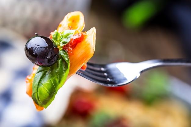 Penne al sugo di pomodoro alla bolognese parmigiano olive nere e basilico su una forchetta
