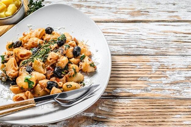 Puttanesca della pasta con il tonno, i pomodori, l'aglio e le olive nere su bianco. vista dall'alto. copia spazio