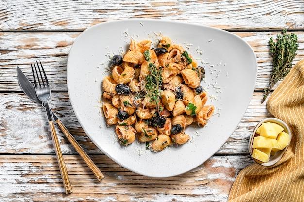 Puttanesca della pasta con il tonno, i pomodori, l'aglio e le olive nere su bianco. vista dall'alto