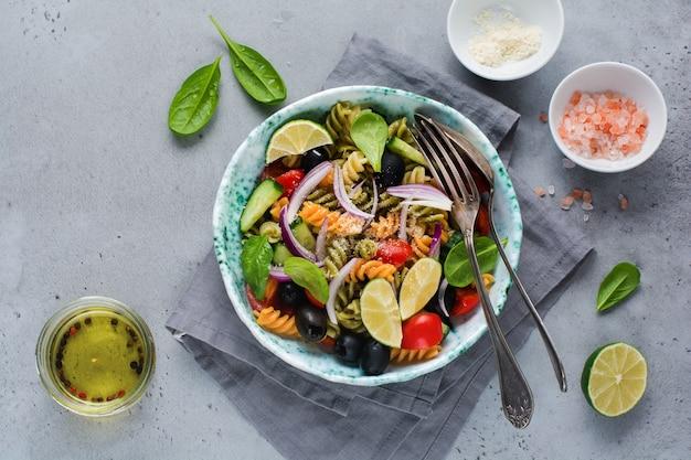 Insalata di pasta con fusilli colorati e verdure in un piatto di ceramica. vista dall'alto.