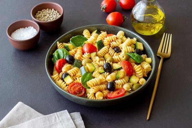 Insalata di pasta con pomodori, zucchine, olive e spinaci. mangiare sano. cibo vegetariano.