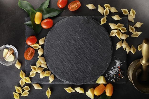 Conchiglie di pasta su pietra nera. pomodori e foglie di alloro con pimento e sale marino e aglio.