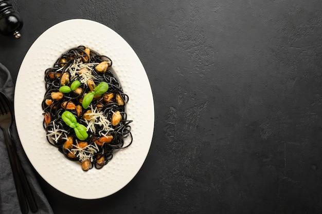Pasta spaghetti al nero di seppia con cozze nel piatto bianco su fondo nero.