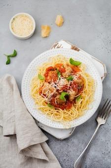Spaghetti di pasta con salsa di pomodoro, parmigiano, basilico e polpette di carne sul piatto in ceramica bianca su cemento grigio o sfondo di pietra