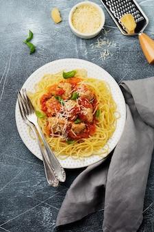 Spaghetti di pasta con salsa di pomodoro, parmigiano, basilico e polpette di carne sul piatto in ceramica bianca su cemento grigio