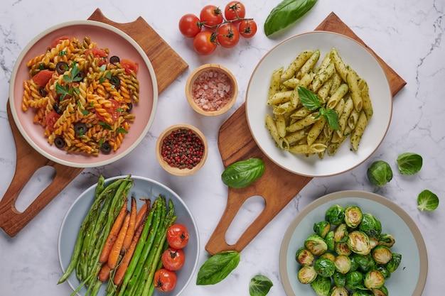 Spaghetti di pasta con zucchine, basilico, panna e formaggio sul tavolo di pietra.
