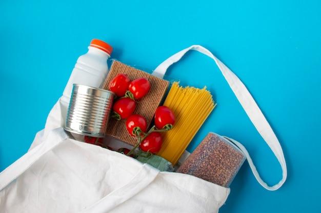 Pasta in umido pomodori latte grano saraceno, elementi essenziali durante la quarantena pandemia covid-19 in un sacchetto bianco di lino