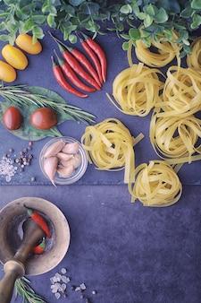 Pasta in tavola con spezie e verdure. tagliatelle con verdure per cucinare su uno sfondo di pietra nera.