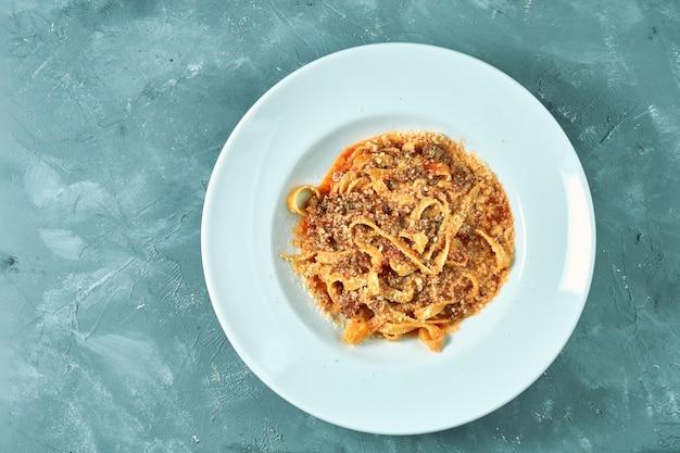 Pasta (tagliatelli) alla bolognese con salsa rossa e carne macinata in un piatto bianco