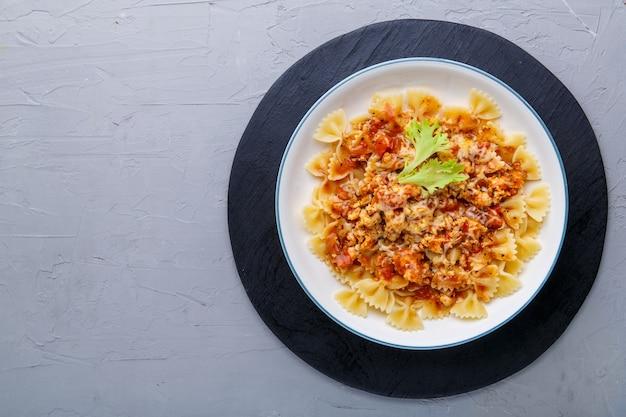 Pasta in salsa di pomodoro bolognese su supporto nero su fondo concreto. copia spazio foto orizzontale