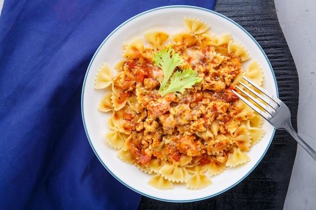 Pasta in salsa di pomodoro bolognese su un supporto nero rotondo su un tovagliolo blu accanto a una forchetta foto orizzontale