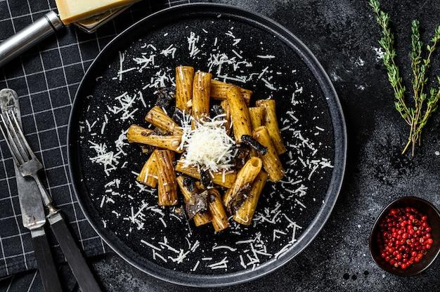 Tortiglioni di pasta al tartufo nero e boletus edulis, funghi bianchi. sfondo nero. vista dall'alto