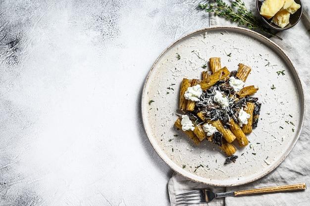 Tortiglioni di pasta al tartufo nero e boletus edulis, funghi bianchi. sfondo grigio. vista dall'alto. spazio per il testo
