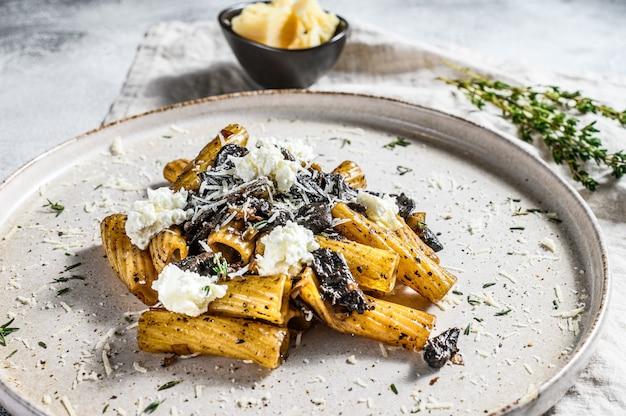 Tortiglioni di pasta al tartufo nero, funghi bianchi, salsa di panna e ricotta. sfondo grigio. vista dall'alto
