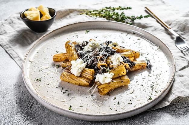 Tortiglioni di pasta al tartufo nero, funghi bianchi, salsa di panna e ricotta.